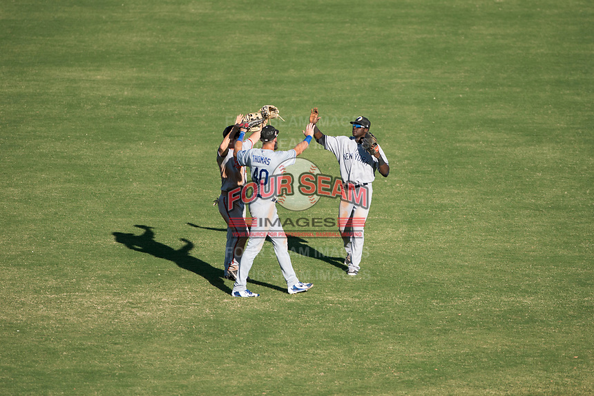 Glendale Desert Dogs outfielders Ryan McKenna (82), Cody Thomas (40), and Estevan Florial (13) celebrate a victory after an Arizona Fall League game against the Mesa Solar Sox at Sloan Park on October 27, 2018 in Mesa, Arizona. Glendale defeated Mesa 7-6. (Zachary Lucy/Four Seam Images)