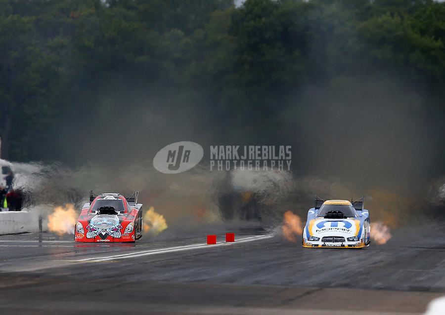 Aug 17, 2014; Brainerd, MN, USA; NHRA funny car driver Matt Hagan (right) races alongside Chad Head during the Lucas Oil Nationals at Brainerd International Raceway. Mandatory Credit: Mark J. Rebilas-