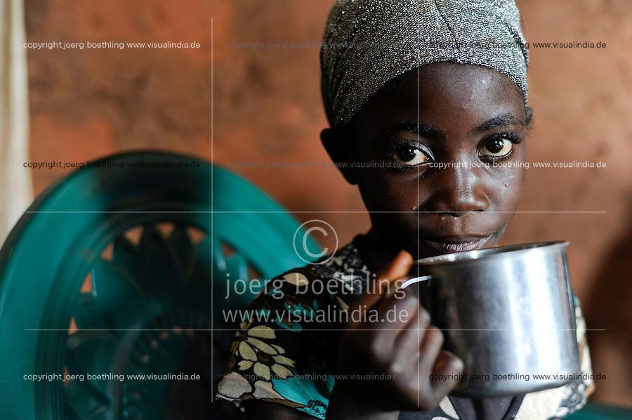 ANGOLA Kwanza Sul, rural development project ACM-KS, girl drinks water from cup in village Cassombo / ANGOLA Kwanza Sul, laendliches Entwicklungsprojekt ACM-KS, Dorf Cassombo, Maedchen trinkt Wasser aus einer Blechtasse