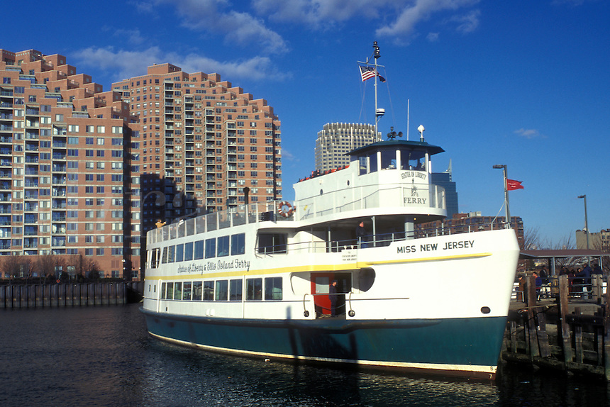 New Jersey, Jersey City, NJ, Liberty State Park, A yellow water taxi leaves the dock on Upper New York Bay transporting passengers to Manhattan, New York. The Statue of Liberty passenger ferry is docked ready for tourists.
