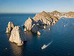 Sea of Cortez, Cabo San Lucas, Mexico; an aerial view of Lands End and the Arch of Cabo San Lucas in early morning sunlight, as fishing boats motor past on their way to the Pacific Ocean, these rocks at the southern most end of the Baja Peninsula separate the Sea of Cortez from the Pacific Ocean