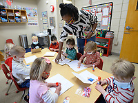 Bridgett Moore, a teacher at First United Presbyterian Church's First School, hands out craft materials Friday, Feb. 12, 2021, to preschool students during a Valentine's Day party at the school in Fayetteville. Students enjoyed a sweet snack before making cards for their parents for Valentine's Day, which is Sunday Visit nwaonline.com/210213Daily/ for today's photo gallery. <br /> (NWA Democrat-Gazette/Andy Shupe)