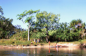 Mato Grosso, Brazil. Rikbaktsa (Canoeiro) Indian family group at the riverside with a dugout canoe.
