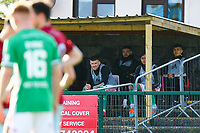 Cork City substitutes (L to R), Steven Beattie, Dylan McGlade, Uniss Kargbo and Jamie Wynne watch the game from the shelter.<br /> <br /> Cobh Ramblers v Cork City, SSE Airtricity League Division 1, 28/5/21, St. Colman's Park, Cobh.<br /> <br /> Copyright Steve Alfred 2021.