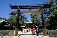 People walk through the entrance to Menji Jingu Shrine in Tokyo, Japan. Japanese shrines are often pagodas, which are usually square and five-storied, are made of wood exhibiting superb carpentry craftsmanship. Tokyo, Japan.