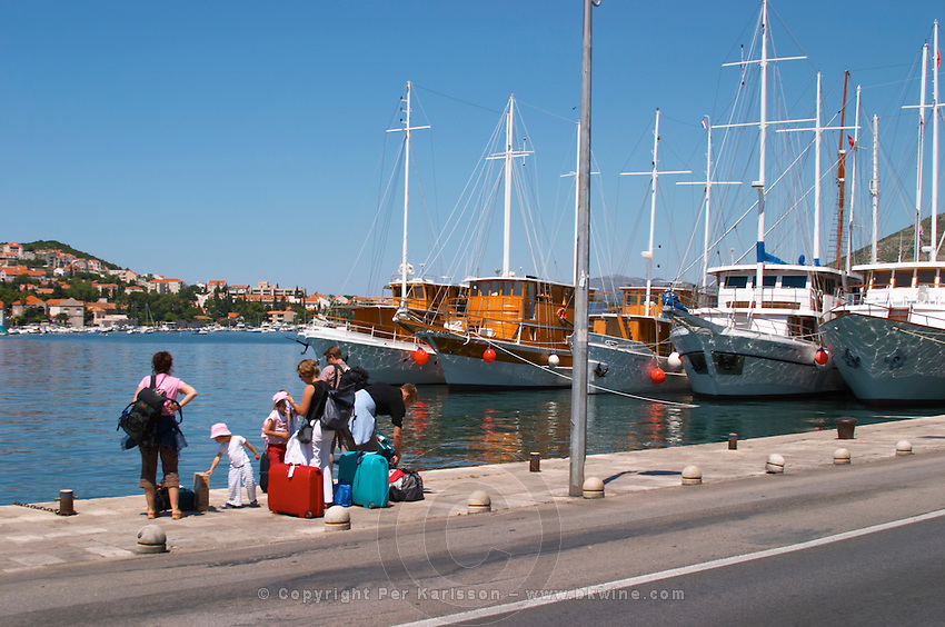 A row of beautiful wooden cruising, sailing and fishing boats ships yachts painted white moored along they key in the harbour. A family waiting at the keyside with several bags and suitcases. Luka Gruz harbour. Dubrovnik, new city. Dalmatian Coast, Croatia, Europe.