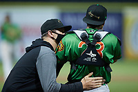 Down East Wood Ducks trainer Derrick Decker checks on catcher Randy Florentino (23) after he was hit in the mask by a foul ball during the game against the Kannapolis Cannon Ballers at Atrium Health Ballpark on May 5, 2021 in Kannapolis, North Carolina. (Brian Westerholt/Four Seam Images)