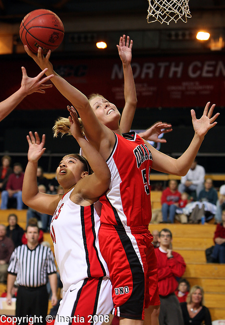 VERMILLION, SD - JANUARY 24:  Jill Wolf #54 of the University of Nebraska Omaha stretches for a rebound over Jasmine Mosley #44 of the University of South Dakota in the first half of their North Central Conference game Thursday night at the DakotaDome in Vermillion. (Photo by Dave Eggen/Inertia)
