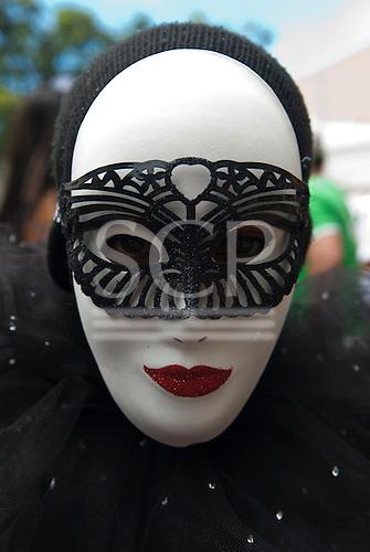 Rio de Janeiro, Brazil. Man wearing white female carnival mask with red glitter lips and black glitter mask.