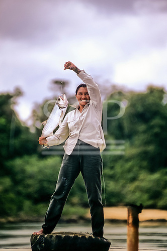 Xingu, Amazon, Brazil. Triumphant smiling Miriam Wapixana with freshly caught river fishPeixe Cachorro, standing on a tyre on a boat.
