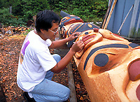 Tsimshian totem pole carver, working on a pole,  Metlakatla, Alaska.