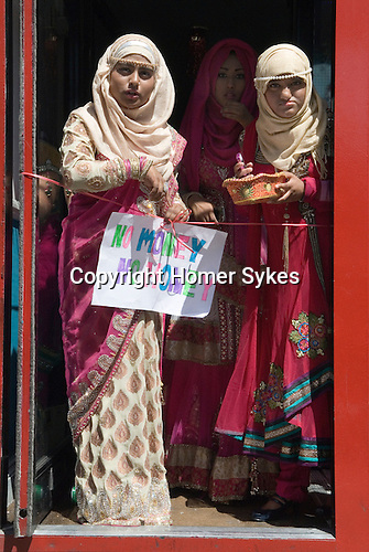 """Muslim women Brick Lane London wait for wedding guests to enter a resturant. The sign she holds reads """"No Money No Honey""""' a tradition in Bengali wedding for the brides relatives to tease the groom into giving a small gift of money, a dowry, once thats done the ribbon is cut and he is allowed in. 2013, 2010s"""