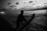 A surfer enters the Mediterranean Sea.