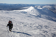 Winter hiker ascending Crawford Path (Appalachian Trail) near the summit of Mount Washington in Sargent's Purchase in the New Hampshire White Mountains during the winter months; this area is part of the Southern Presidential Range.