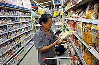 An elder lady checks a pack of oats in Wumart supermarket in Beijing, China. China's inflation rate last month soared to its highest level in more than a decade, sounding new alarm bells that will likely lead to further monetary tightening..13 Aug 2007