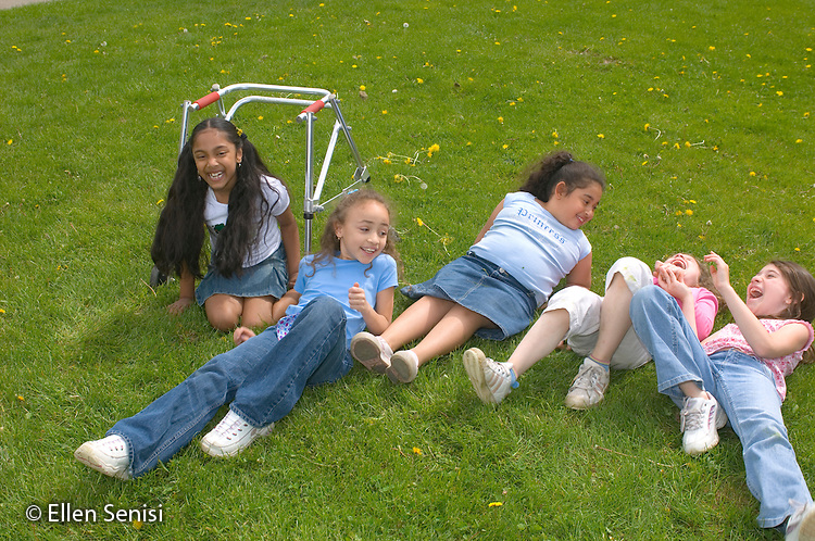 MR / Schenectady, NY.Zoller school (urban public school) / grade 2 Inclusion class.Friends laugh and play on playground. (Girl with walker: 7, cerebral palsy; girl with light blue shirt and denim skirt: 8, African-American / Puerto-Rican / Caucasian, Congenital Heart Disease, Hip Dysplasia).MR: AG-gss, Cha9, Gar6.© Ellen B. Senisi