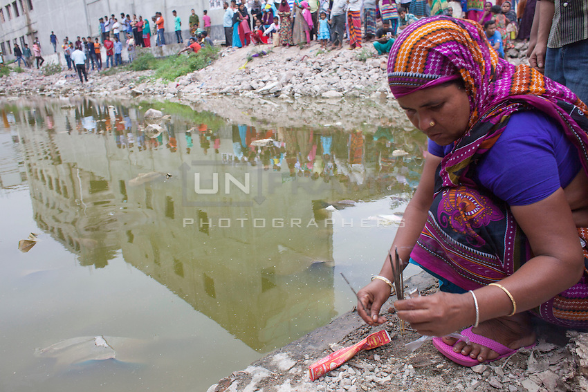 Relative of a victim killed in the collapse of Rana Plaza sits pay her tribute in front of the collapse site in Savar, near Dhaka, Bangladesh