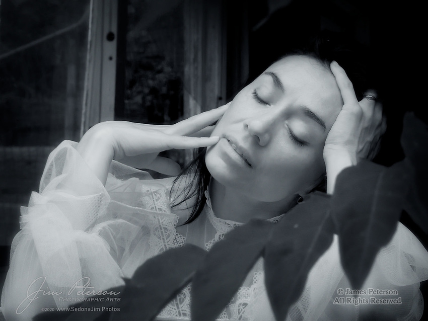 Ambivalence (Infrared).  Posing in the window of an abandoned house, our beautiful model shows us…  what?  Is she meditating?  Reminiscing?  Worrying?  Longing for someone far away?  She didn't say, and we'll keep wondering.<br /> <br /> This image was captured during a workshop offered by Red Bench Photo Studio in Jerome, Arizona (the state's most populous ghost town).  It was made possible by our very talented model, Nova Delaube, who always knows what to do during a photo shoot.<br /> <br /> Image ©2020 James D. Peterson