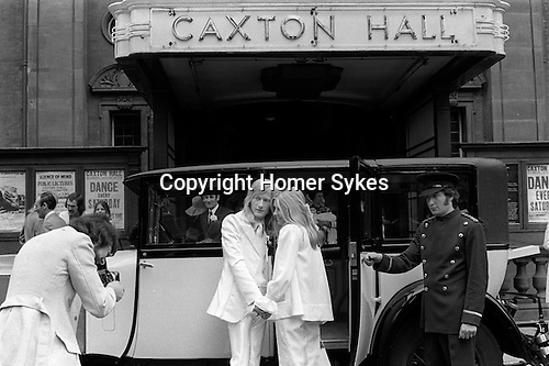 Caxton Hall, Westminster London. London's main registry office until 1979. White wedding, his and her uni sex clothes, she is wearing a trouser suit. rather than a wedding dress, very fashionable at that time. 1970s London ..<br /> He is Michael Stephens I think a well know hairdresser of the time. If you know otherwise please let me know.