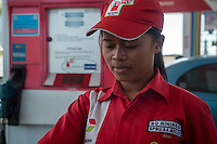 Bali, Indonesia.  Young Balinese Female Gas Station Attendant.
