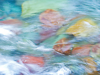 Water rushing over colorful river rocks at Rising Sun Creek, Glacier National Park