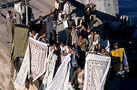 Craft sellers displaying tablecloths for tourists on board a cruise ship sailing the Nile, Esna, Egypt.