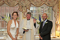 Bride and groom standing with priest looking out at guests smiling.