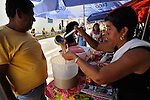A street vendor laddles juice from her stall in a street market in the peaceful, hilltop town of Suchitoto, El Salvador..
