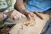 Cuba, Havana.  Partagas Cigar Factory.  Woman Cigar Maker (Torcedor) Uses the Blade (Chaveta) to Trim the Leaf.