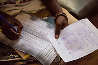 Senegal, Touba.  Student Holding English Test Results, Entering Grade on Score Sheet.