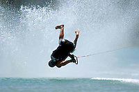 A barefoot skier does a manouver over the wake.