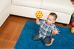 12 month old baby boy kneeling on floor, holding ball up ready to throw