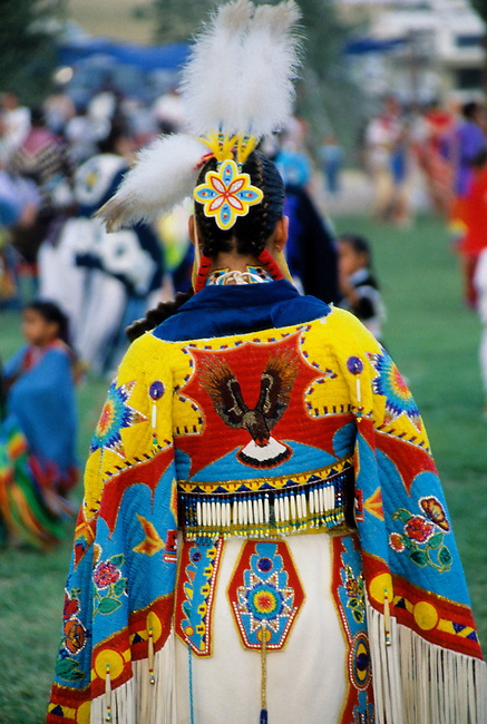 Ladies traditional Pow Wow dancer dressed in white brain tanned leather regalia with beautiful beaded cape with an eagle motif along with a beaded hair barret holding 3 eagle plumes for a headdress at the Chippewa-Cree pow wow on the Rocky Boy Indian Reservation, Montana
