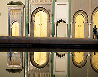Man standing by pool, reflection of building in water, Dar el-Makhzen