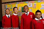K-8 Parochial School Bronx New York Grade 4 portrait of 2 boys and 2 girls differing heights standing in hallway horizontal