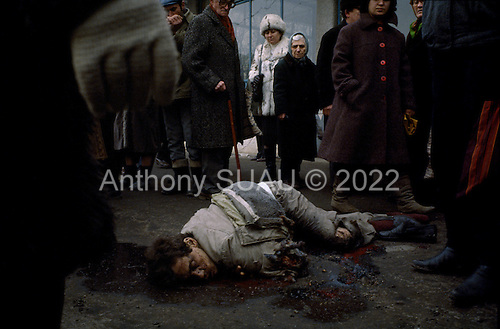 """Bucharest, Romania<br /> December 1989<br /> <br /> Romanians look down with hatred at the corpse of a suspected Securitate member - former leader Nicolae Ceausescu's secret police.<br /> <br /> The week-long series of violence that overthrew the Communist regime of Nicolae Ceausescu, ended in a trial and execution of Ceausescu and his wife Elena by firing squad. Romania was the only Eastern Bloc country to violently overthrow its Communist regime or to execute its leaders.<br /> <br /> The Romanian populace was dissatisfied with the Communist regime and leader Ceausescu's economic and development policies were blamed for the country's shortages and widespread poverty. The powerful secret police (Securitate) controlled what was essentially a police state. Ceausescu was not pro-Soviet but """"independent"""" on foreign policy. He imitated the hard-line, megalomania, and personality cults of communist leaders like North Korea's Kim Il Sung."""