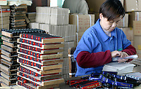 A worker sorts and boxes a stack of harmonicas at the Shanghai General Harmonica Factory (SGHF) in Shanghai, China. Although it makes well-respected brands such as the Huang, Suzuki, and Hohner that are favored by many professional musicians around the world, the 60 years old state owned SGHF had to trim down its work force from 800 in the mid 1980's to just over 100 today..23-FEB-04