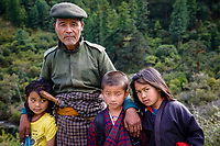 A Bhutanese forester with his three children on the mountain roadside between Nubding and Dungdeng Ngesa, Central Bhutan