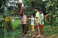 INDIA Karnataka, farm near Mangalore, farmer cut fresh coconut for children to drink / INDIEN, Farm bei Mangalore, Farmer oeffnet eine frische Kokosnuss fuer Kinder zum Trinken