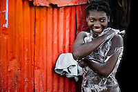 A Haitian girl has a bath in a shanty town inside the La Saline market, Port-au-Prince, Haiti, 14 July 2008. Every day thousands of women from all over the city of Port-au-Prince try to resell supplies and food from questionable sources in the La Saline market. The informal sector significantly predominate within the poor Haitian economics and the regular shops virtually do not exist. La Saline is the largest street market area in Port-au-Prince.