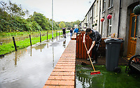 Flooding effected the villages of Aberdulais and Tonna in the Neath Valley after Storm Callum brought heavy rain and wind to the area cuasing the River Neath to reach bursting point.L<br /> Luke Griffiths sweeps away water from his family home at Canal Side, Tonna, Neath. Saturday 13 October 2018