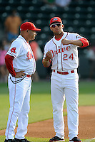 Second baseman Yoan Moncada (24) of the Greenville Drive, right, talks with hitting coach Nelson Paulino  in a game against the Charleston RiverDogs on Sunday, May 24, 2015, at Fluor Field at the West End in Greenville, South Carolina. The Cuban-born 19-year-old Red Sox signee has been ranked the No. 1 international prospect in baseball by Baseball America. Charleston won 3-2. (Tom Priddy/Four Seam Images)