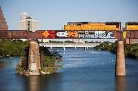 Train with graffiti runs on the Union Pacific Train Tressel Bridge over Lake Austin