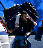 Pictured: A migrant man carries his belongings at the refugee camp Tuesday 23 February 2016<br /> Re: Migrants at a refugee camp in the Schisto area of Athens, Greece.