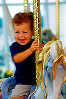 Portrait of a smiling toddler boy with curly red hair as he rides on a carousel pony. Ben. Georgia.