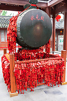 Nanjing, Jiangsu, China.  Drum in the Drum Pavilion of the Confucian Temple Complex.  Red Tags and Tassles are Prayers for Good Luck.