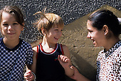 Romania. Three schoolgirls in the playground smiling at each other, one blonde, one with black hair and one brunette.