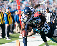 CHARLOTTE, NC - DECEMBER 15: Chris Carson #32 of the Seattle Seahawks scores a touchdown over Tre Boston #33 of the Carolina Panthers during a game between Seattle Seahawks and Carolina Panthers at Bank of America Stadium on December 15, 2019 in Charlotte, North Carolina.