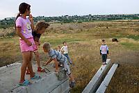 REPUBLIC OF MOLDOVA, Gagauzia, Vulcanesti, 2009/06/29..Vulcanesti children play among the ruins of farm ruins of the Soviet era. For many of them, their parents work in Russia or Turkey..© Bruno Cogez / Est&Ost Photography..REPUBIQUE MOLDAVE, Gagaouzie, Vulcanesti, 29/06/2009..Les enfants de Vulcanesti jouent parmi des ruines de batiments agricoles de l'epoque sovietique. Pour beaucoup d'entre-eux, leurs parents travaillent en Russie ou en Turquie..© Bruno Cogez / Est&Ost Photography