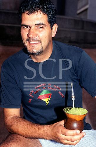 Porto Alegre, Brazil. Gaucho man wearing a Rio Grande do Sul t-shirt holding a chimarrao, traditional mate tea vessel.